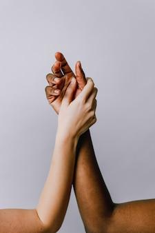 Ramiona czarno-białych kobiet. koncepcja integracji rasowej, prawa człowieka, równość społeczna