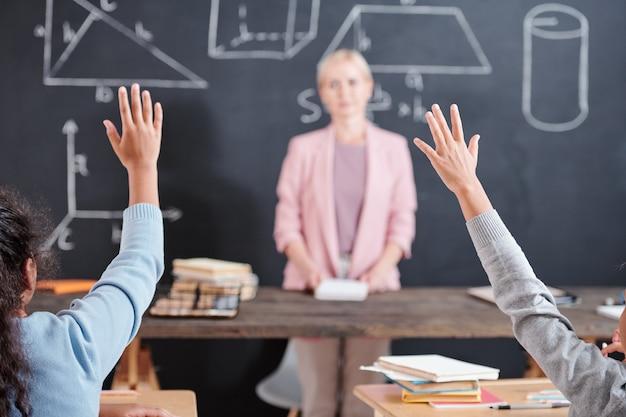 Ramiona dwóch sprytnych uczniów, którzy chcą odpowiedzieć na pytanie nauczyciela stojącego na tablicy z geometrycznymi kształtami na lekcji