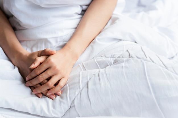 Ramiona kobiety na łóżku z białym kocem rano.