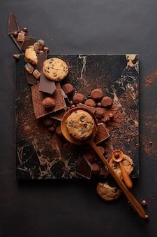 Ramka domowych ciasteczek z czekoladkami i cukierkami na marmurowej tacy i czarnym tle
