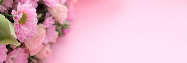 Ramka fioletowe i różowe chryzantemy, orchidea i różne kwiaty na różowym tle.