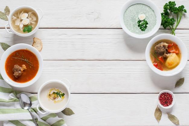 Ramka gorących zup na czczo na białym wolnej przestrzeni drewna. restauracja serwująca menu obiadowe, mieszkanie