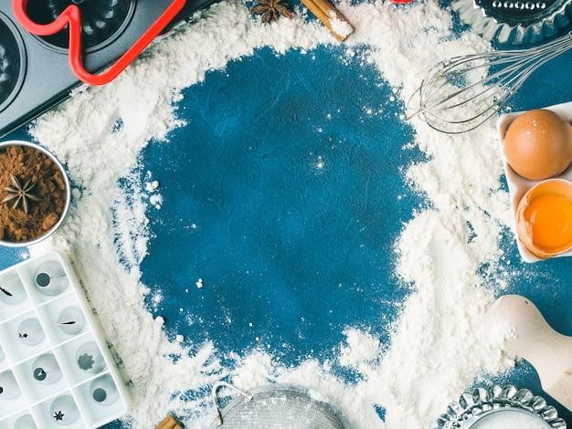 Ramka mąki tło do pieczenia na ciemnoniebieskim z akcesoriami do narzędzi