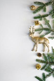 Ramka na nowy rok lub boże narodzenie składa się z ozdób choinkowych, kulek, złotych koralików, prezentów, świateł i gałęzi jodłowych na białym tle. pozycja płaska, widok z góry, miejsce.