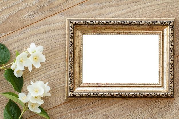 Ramka na zdjęcia archiwalne z miejsca kopiowania i kwiaty jaśminu na drewnianych deskach. widok z góry.