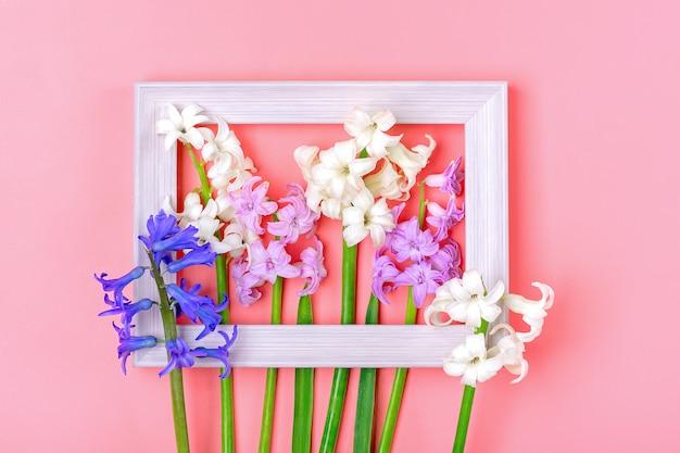 Ramka na zdjęcia i bukiet wiosennych kwiatów białych i liliowych hiacyntów na białym tle