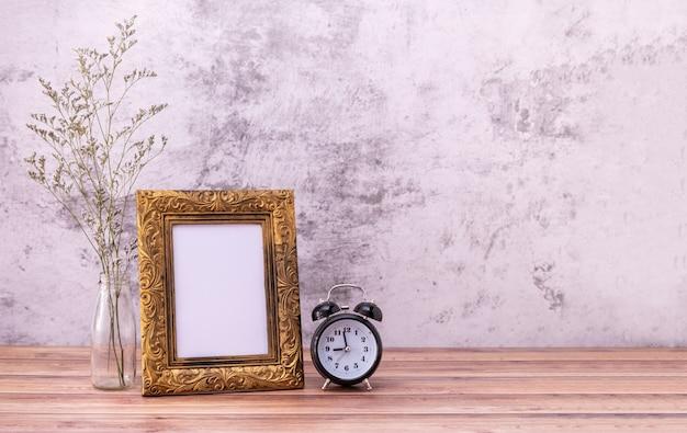 Ramka na zdjęcia i kwiaty i zegar na drewnianym stole