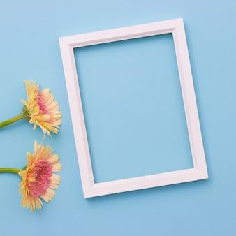 Ramka na zdjęcia i żółty kwiat na jasnym niebieskim tle. letnie płaskie mieszkanie.
