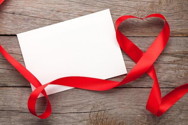 Ramka na zdjęcia lub karta podarunkowa z wstążką w kształcie serca walentynki na tle drewnianego stołu