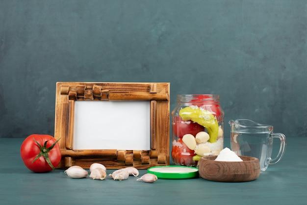 Ramka na zdjęcia, marynowana w szklanym słoju, sól i świeże warzywa na niebieskim stole.