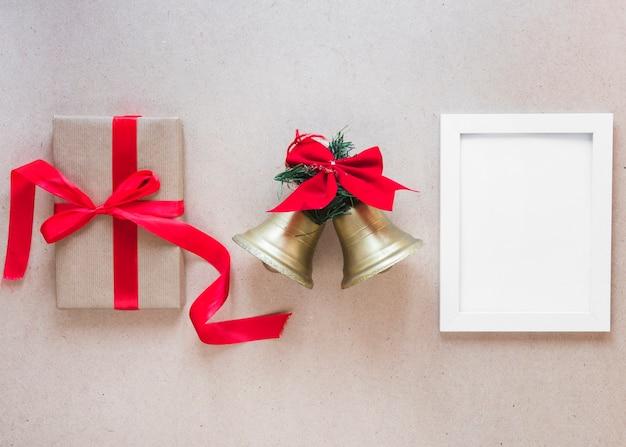 Ramka na zdjęcia między dzwonkami świątecznymi a pudełkiem prezentowym