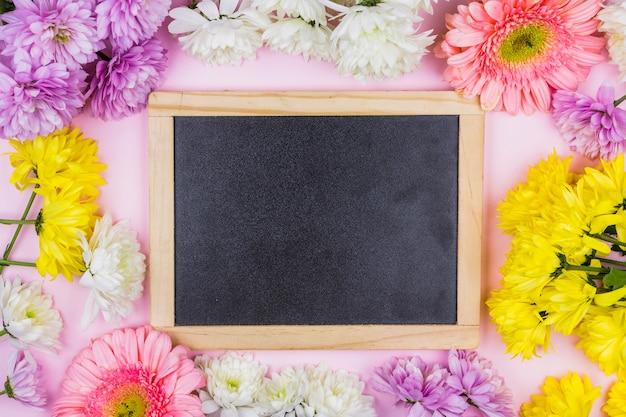 Ramka na zdjęcia między jaskrawymi świeżymi kwiatami