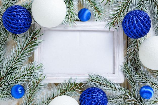 Ramka na zdjęcia między świąteczną dekoracją, z białymi i niebieskimi kulkami na białym drewnianym stole. widok z góry, ramka do skopiowania miejsca