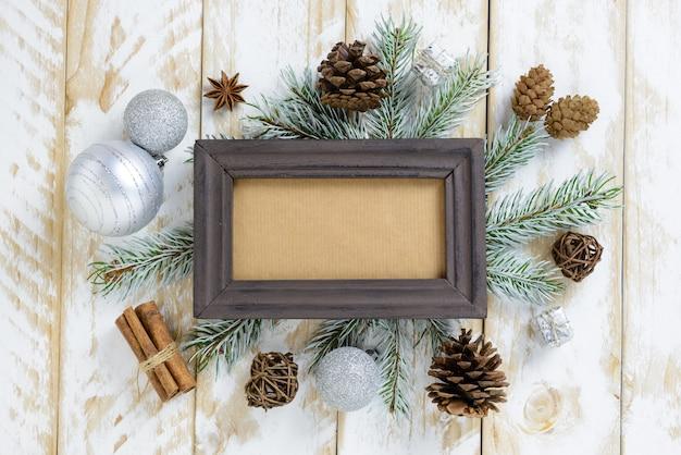 Ramka na zdjęcia między świąteczną dekoracją, z białymi kulkami i szyszkami na białym drewnianym stole. widok z góry, ramka do skopiowania miejsca