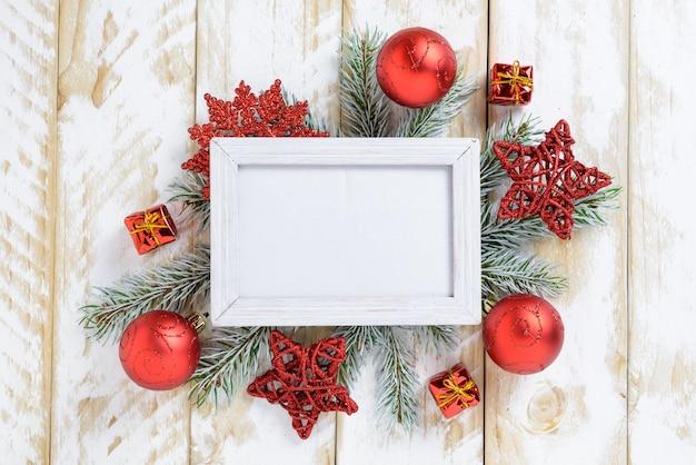 Ramka na zdjęcia między świąteczną dekoracją, z czerwonymi kulkami i gwiazdkami na białym drewnianym stole. widok z góry, ramka do skopiowania miejsca