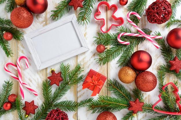 Ramka na zdjęcia między świąteczną dekoracją, z czerwonymi kulkami i laską cukrową na białym drewnianym stole. widok z góry, ramka do skopiowania miejsca.