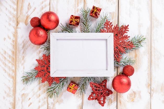 Ramka na zdjęcia między świąteczną dekoracją, z czerwonymi kulkami i płatkami śniegu na białym drewnianym stole. widok z góry, ramka do skopiowania miejsca
