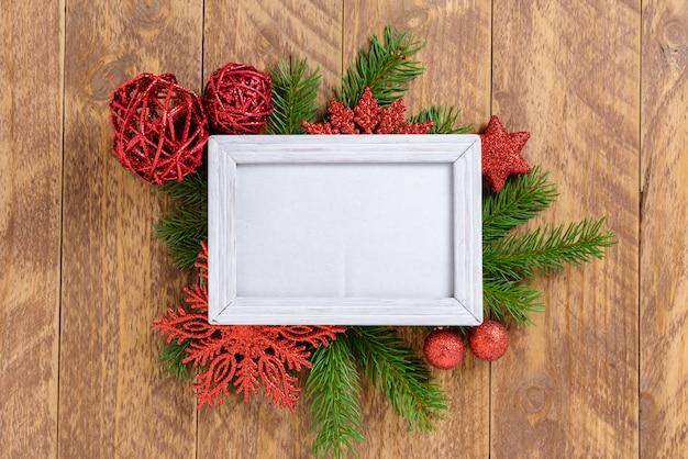 Ramka na zdjęcia między świąteczną dekoracją, z czerwonymi kulkami i płatkami śniegu na brązowym drewnianym stole. widok z góry, ramka do skopiowania miejsca