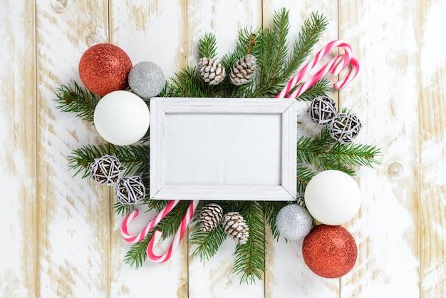 Ramka na zdjęcia między świąteczną dekoracją, z kolorowymi kulkami i laską cukrową na białym drewnianym stole. widok z góry, ramka do skopiowania miejsca.