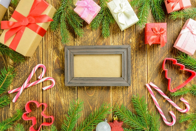 Ramka na zdjęcia między świąteczną dekoracją, z pudełkami prezentowymi i laską cukrową na brązowym drewnianym stole. widok z góry, ramka do skopiowania miejsca.