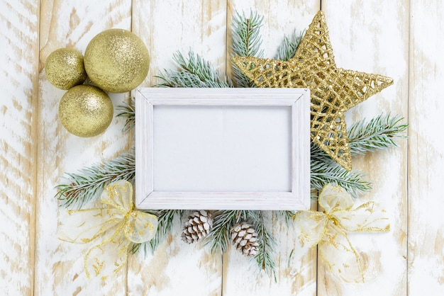 Ramka na zdjęcia między świąteczną dekoracją, ze złotymi kulkami i gwiazdą na białym drewnianym stole. widok z góry, ramka do skopiowania miejsca