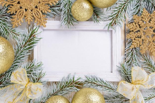 Ramka na zdjęcia między świąteczną dekoracją, ze złotymi kulkami i płatkami śniegu na białym drewnianym stole. widok z góry, ramka do skopiowania miejsca