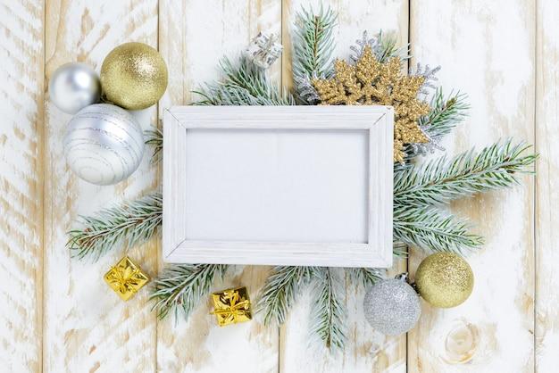 Ramka na zdjęcia między świąteczną dekoracją, ze złotymi kulkami i pudełkiem na białym drewnianym stole. widok z góry, ramka do skopiowania miejsca