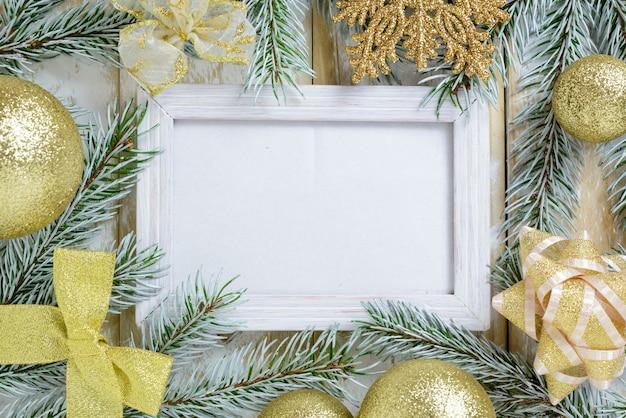 Ramka na zdjęcia między świąteczną dekoracją, ze złotymi kulkami i wstążkami na białym drewnianym stole. widok z góry, ramka do skopiowania miejsca