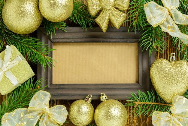 Ramka na zdjęcia między świąteczną dekoracją, ze złotymi kulkami i wstążkami na brązowym drewnianym stole. widok z góry, ramka do skopiowania miejsca.