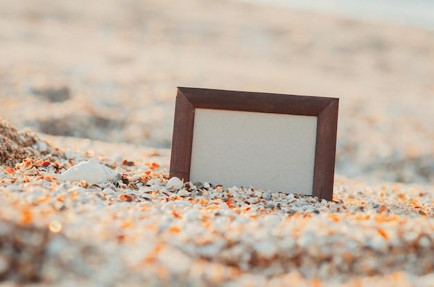 Ramka na zdjęcia na tle piasku latem, morze w miejscu zachodu słońca na napis