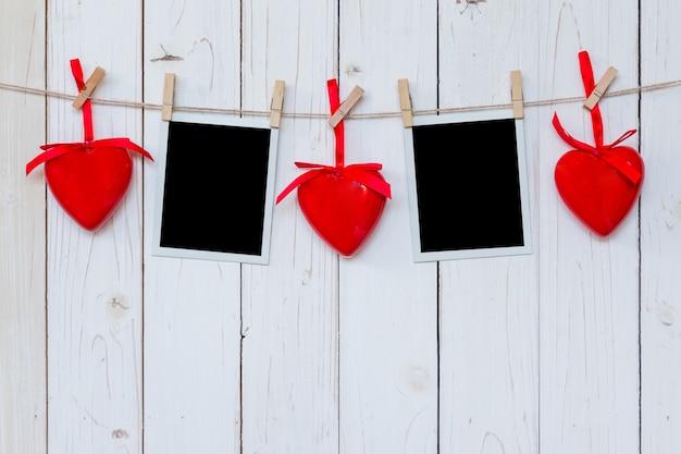 Ramka na zdjęcia puste i czerwone serce wiszące na białym tle drewna z miejsca
