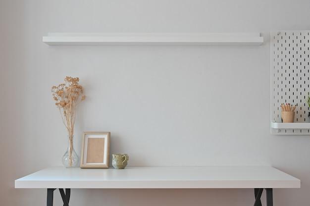 Ramka na zdjęcia w miejscu pracy, kawa, suchy kwiat z półkami i tablicą na kołki.