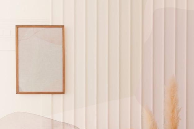 Ramka na zdjęcia wisząca na białej ścianie przy wyschniętej trawie pampasowej