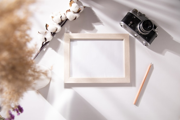 Ramka na zdjęcia z bawełną i aparatem na stole