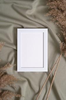 Ramka na zdjęcia z makietą pustej karty papieru w pobliżu suchej trawy pampasów na zielonej neutralnej kolorowej tkaninie