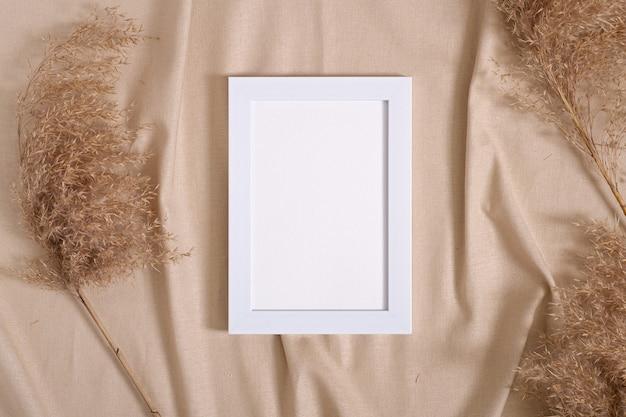 Ramka na zdjęcia z makietą pustej karty papieru w pobliżu suchej trawy pampasowej na beżowym neutralnym kolorze tkaniny