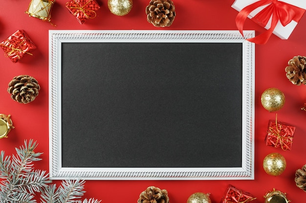 Ramka na zdjęcia z wolną czarną przestrzenią wokół ozdób choinkowych i prezentów na czerwonym tle
