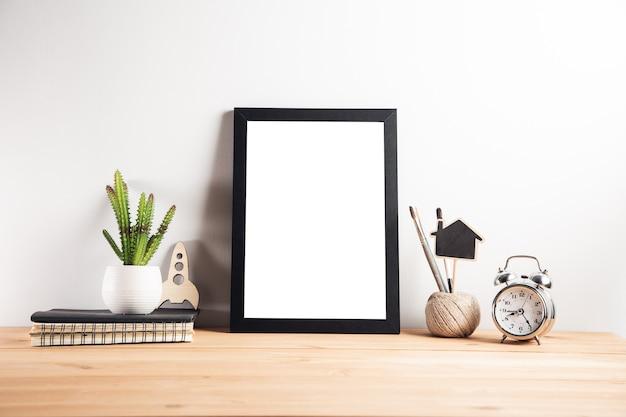 Ramka na zdjęcia z zegarem i kaktusem na stole roboczym
