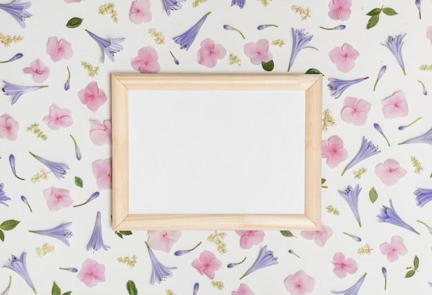 Ramka na zdjęcie między kolekcją wspaniałych kwiatów fioletowych i zielonych liści