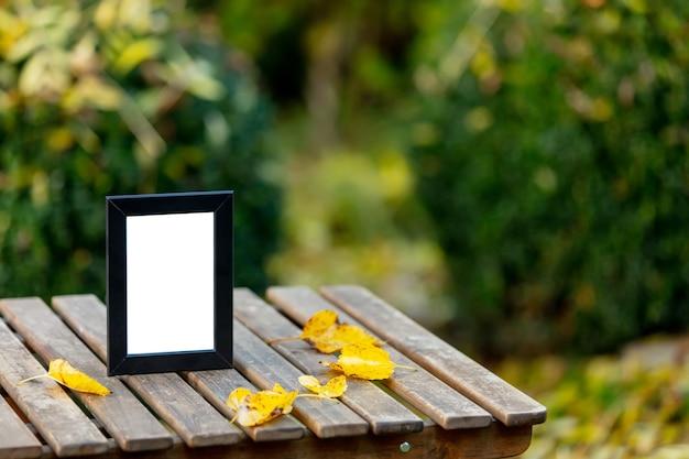 Ramka na zdjęcie na drewnianym stole w ogrodzie