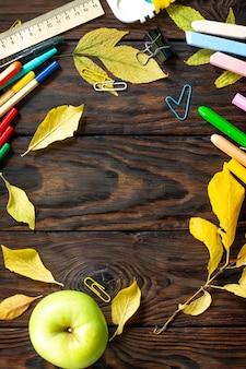 Ramka powrót do szkoły stół z jesiennymi liśćmi jabłko i przybory szkolne widok z góry