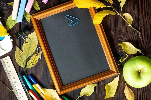 Ramka powrót do szkoły stół z notatnikiem z jesiennych liści jabłko i przybory szkolne