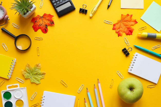 Ramka przybory szkolne zeszyty ołówki i długopisy spinacze do papieru farby szkło powiększające jabłko