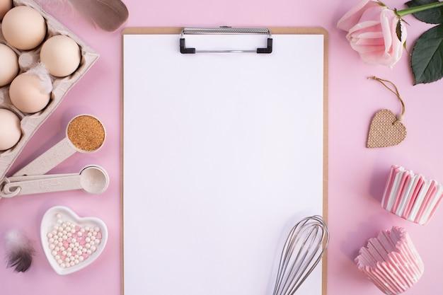 Ramka składników do pieczenia na delikatnie różowym, pastelowym stole. gotowanie na płasko leżało z miejscem na kopię. widok z góry. koncepcja pieczenia. leżał płasko