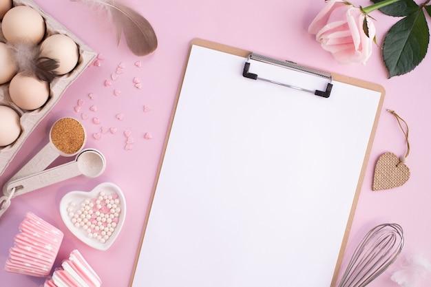 Ramka składników spożywczych do pieczenia na delikatnie różowej, pastelowej powierzchni