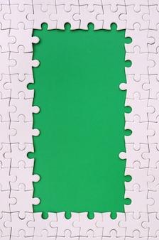 Ramka w formie prostokąta, wykonana z białej układanki wokół zielonej przestrzeni