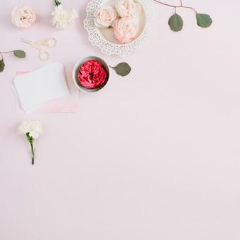 Ramka w kwiaty z beżowo-czerwonych róż i białego goździka na bladym, pastelowym różu