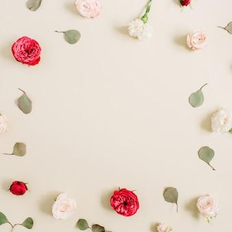 Ramka w kwiaty z beżowo-czerwonych róż, liść eukaliptusa na bladym pastelowym beżu. widok z góry na płasko. rama wieniec kwiatowy.