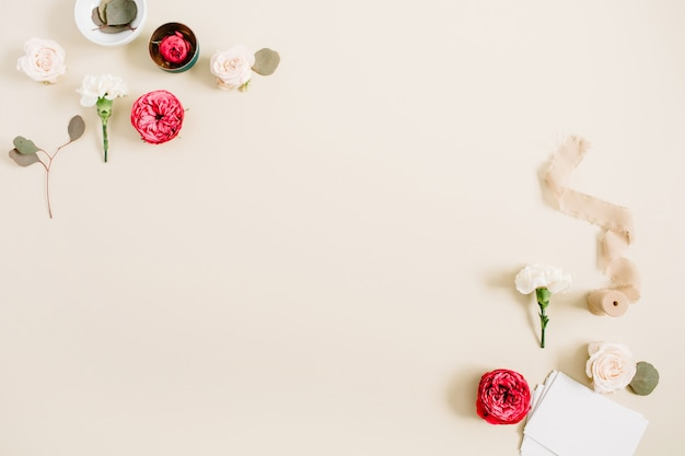 Ramka w kwiaty z beżowych i czerwonych róż oraz białego goździka na bladym pastelowym beżu
