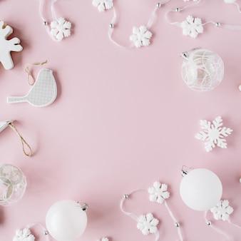 Ramka wykonana z białej dekoracji świątecznej z bombkami, świecidełkiem, kokardką, łosiem, ptaszkiem na różu